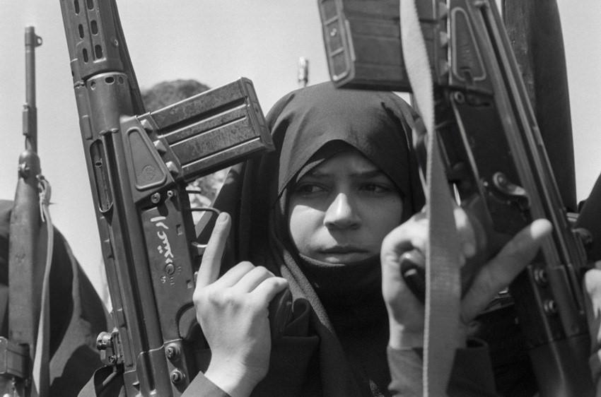 Una mujer sosteniendo un arma